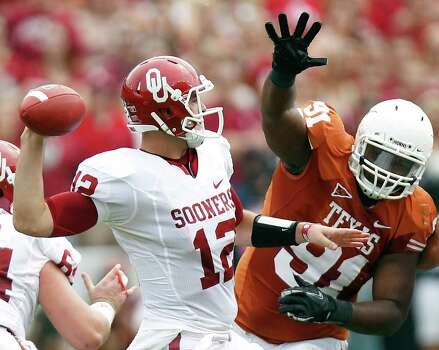In this Oct. 8, 2011, file photo, Oklahoma quarterback Landry Jones (12) passes under pressure from Texas defensive tackle Kheeston Randall (91) during the first half of an NCAA  college football game at the Cotton Bowl in Dallas. Photo: Mike Fuentes, Associated Press / FR103746 AP