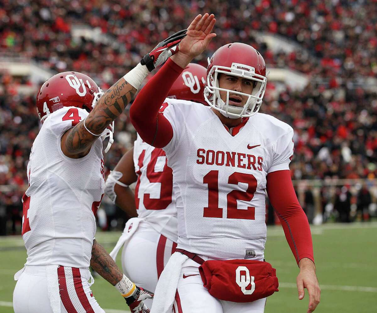 Oklahoma's Landry Jones (12) and Kenny Stills (4) celebrate after Oklahoma scored a touchdown against Texas Tech during an NCAA college football game in Lubbock, Saturday, Oct. 6, 2012.