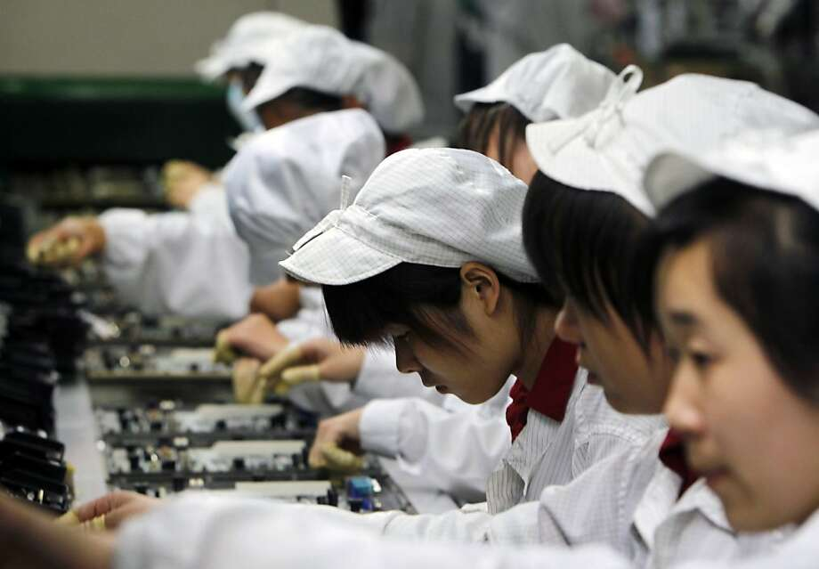 Employees work on the production line at the Foxconn complex in Shenzhen, China. Foxconn is the company that makes Apple's iPhones. Photo: Kin Cheung, Associated Press