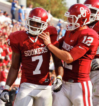 Oklahoma running back DeMarco Murray (left) and quarterback Landry Jones celebrate after a touchdown by Murray against Air Force in the fourth quarter of an NCAA college football game in Norman, Okla., Saturday, Sept. 18, 2010. Oklahoma won 27-24. Photo: Sue Ogrocki, Associated Press / AP