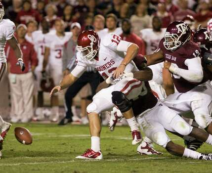 Oklahoma quarterback Landry Jones (12) fumbles after being hit by Texas A&M's Von Miller (40) in the second quarter during an NCAA college football game Saturday, Nov. 6, 2010, in College Station. Oklahoma recovered the fumble. Photo: Steve Campbell, Associated Press / FR170187 AP