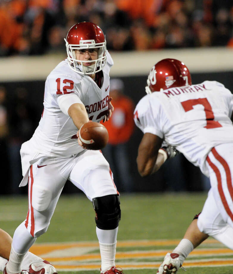 Oklahoma quarterback Landry Jones (left) hands off to running back DeMarco Murray during first half of an NCAA college football game against Oklahoma State in Stillwater, Okla., Saturday, Nov. 27, 2010. Photo: Brody Schmidt, Associated Press / FR79308 AP