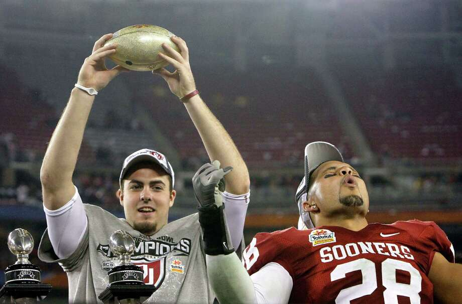 Oklahoma's Landry Jones (left) holds up part of the championship trophy as teammate Travis Lewis (28) shouts after a Fiesta Bowl NCAA college football game victory against Connecticut Saturday, Jan. 1, 2011, in Glendale, Ariz. Oklahoma defeated Connecticut 48-20. Photo: Ross D. Franklin, Associated Press / AP