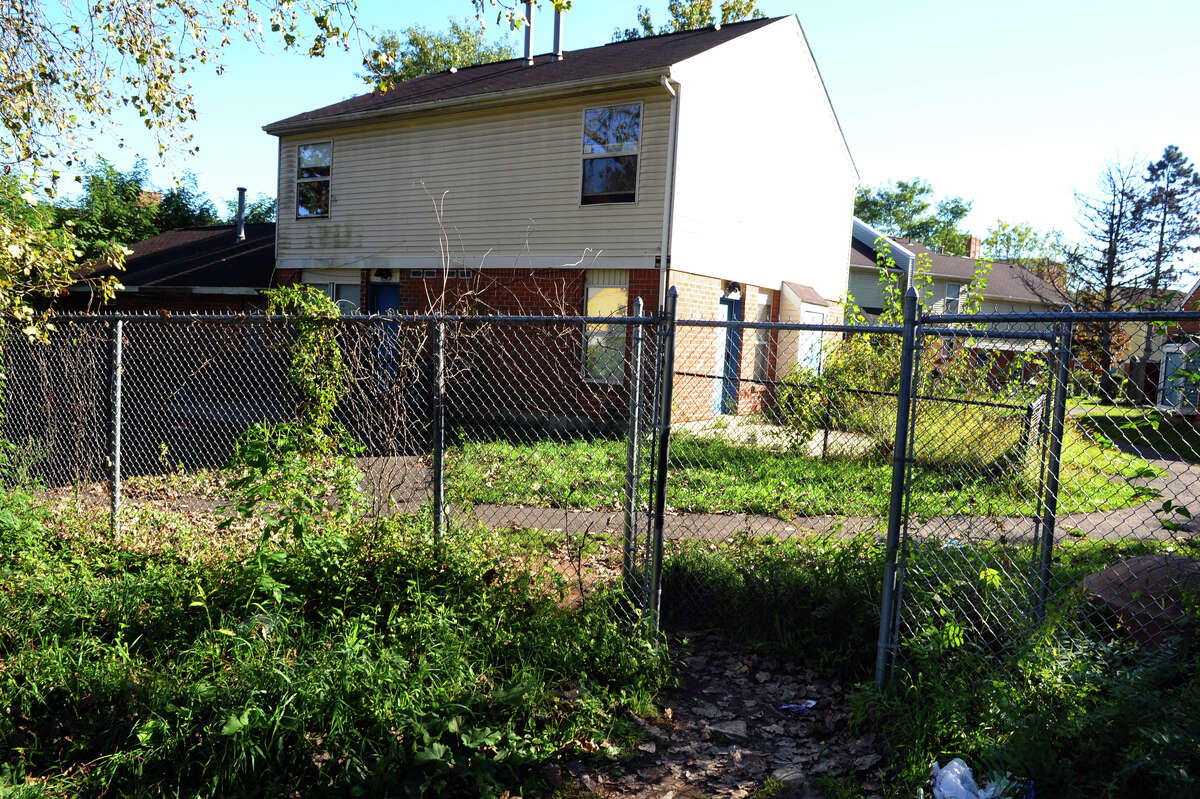A view of Trumbull Gardens housing complex and fence with an opening along Sunshine Circle in Bridgeport, Conn. on Thursday October 11, 2012. A man was found shot to death in his car which was parked along this quiet street.