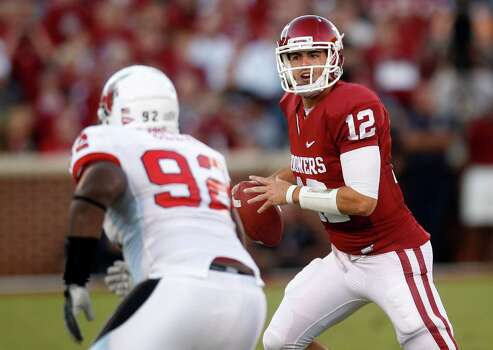Oklahoma quarterback Landry Jones (right) looks for a receiver during the first quarter of an NCAA college football game against Ball State in Norman, Okla., Saturday, Oct. 1, 2011. Photo: Sue Ogrocki, Associated Press / AP