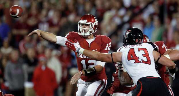 Oklahoma quarterback Landry Jones passes under pressure from Texas Tech defensive end Jackson Richards in the first quarter of an NCAA college football game in Norman, Okla., Saturday, Oct. 22, 2011. Photo: Sue Ogrocki, Associated Press / AP
