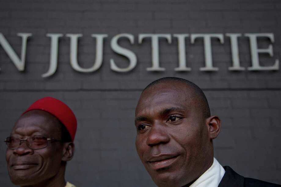 Alali Efanga, right, and Chief Fidelis A. Oguru, plaintiffs in the court case of Nigerian farmers against Shell, wait for the start of their case in The Hague, Netherlands, Thursday Oct. 11, 2012. Nigerian farmers are suing Shell in a Dutch court, asking judges to order the oil multinational to clean up environmental damage the farmers say is caused by leaking pipes. Thursday's case in The Hague Civil Court is a legal landmark in the Netherlands as it marks the first time a Dutch company has been sued for alleged environmental mismanagement caused by an overseas subsidiary. (AP Photo/Peter Dejong) Photo: Peter Dejong / AP