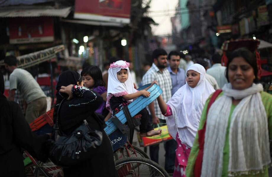 A young Muslim girl waits to be lifted down from a cycle rickshaw on International Day of the Girl Child in New Delhi. In India, with 914 girls under age 6 for every 1,000 boys, discrimination happens through abortions of female fetuses. Photo: Altaf Qadri / AP