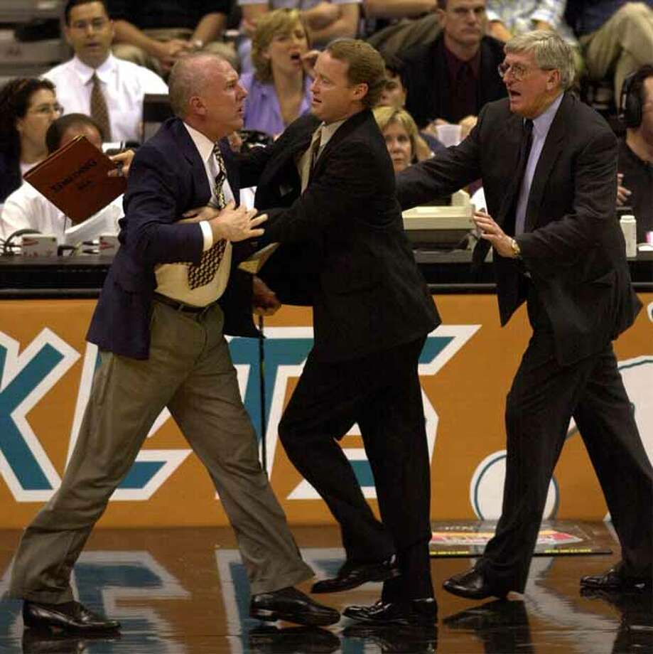 Spurs head coach Gregg Popovich is restrianed by assistant coach Mike Budenholzer and Hank Egan after Popovich protested a flagrant foul call on Danny Ferry at the Alamodome on Monday, May 7, 2001. Popovich received a douvle technical and was ejected in the 2nd quarter.   Kin Man Hui/staff. Photo: KIN MAN HUI, San Antonio Express-News / San Antonio Express-News