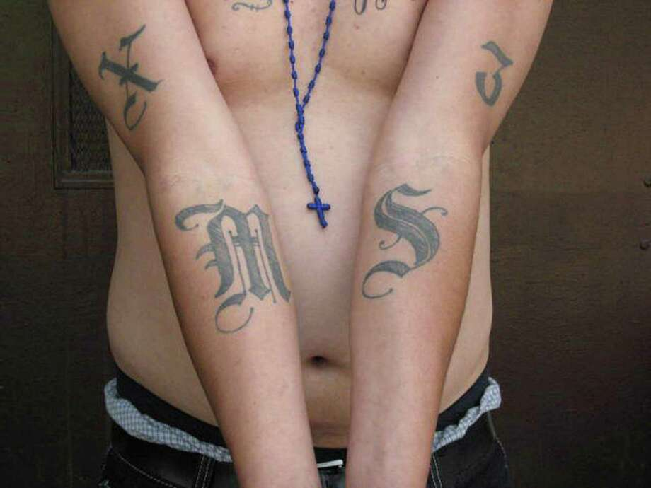 Members of MS-13, or Mara Salvatrucha, often wear distinctive tattoos as seen in this INS handout photo. Photo: Michael Johnson / U.S. IMMIGRATION AND CUSTOMS ENF