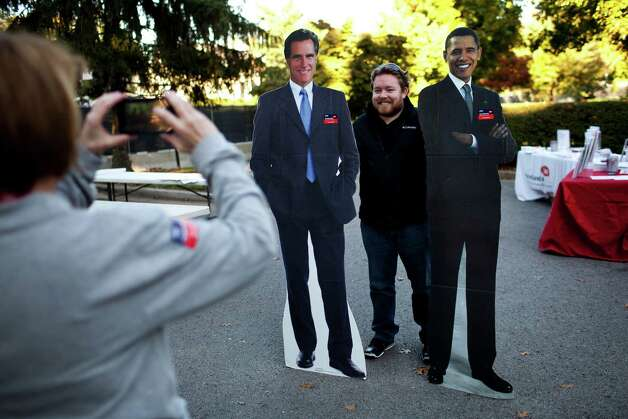 Adam Jones poses for a photo with cardboard cutouts of President Barack Obama and Republican challenger Mitt Romney prior to the vice presidential debate at Centre College in Danville, Ky., Oct. 11, 2012. The debate between Vice President Joe Biden and Rep. Paul Ryan (R-Wis.), the Republican vice presidential candidate, will be split into nine, 10-minute segments, with Martha Raddatz, the moderator, choosing the topics for each. (Max Whittaker/The New York Times) Photo: MAX WHTTAKER, STR / NYTNS