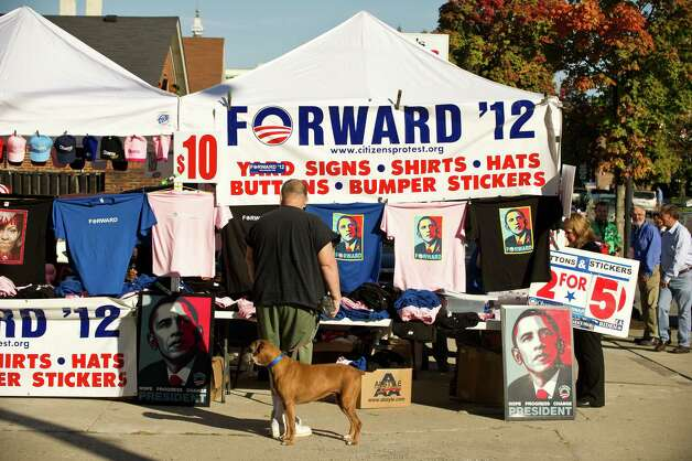 A man walking his dog looks at merchandise in support of US President Barack Obama before the vice presidential debate at Centre College in Danville, Kentucky, on October 11, 2012.    AFP PHOTO/Nicholas KAMMNICHOLAS KAMM/AFP/GettyImages Photo: NICHOLAS KAMM, Staff / AFP