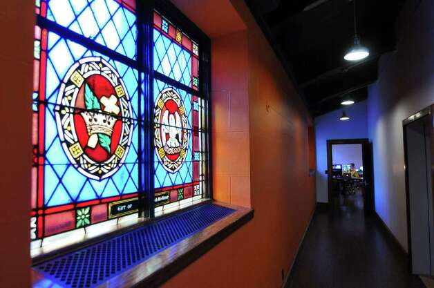 An original stained glass window remains in what is now a hallway to the public relations office of Overit Media's new home on New Scotland Avenue, in what used to be the sanctuary of the former St. Teresa of Avila church on Monday Oct. 8, 2012 in Albany, NY.  (Philip Kamrass /  Times Union) Photo: Philip Kamrass / 00019569A