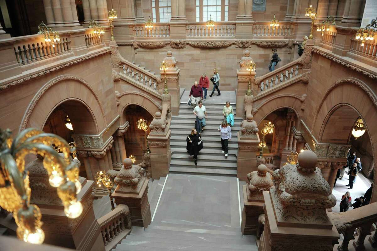Maeve McEneny, bottom left, a Capitol tour guide, walk down the Million Dollar Staircase as she leads a ?Capitol Hauntings? tour of the New York State Capitol on Thursday, Oct. 11, 2012 in Albany, NY. The annual tours explore the legends, folklore and ghost stories connected to the Capitol. The Capitol Hauntings tours are free and open to the public with tours being offered at noon and 5:30 p.m. Monday through Friday (except Columbus Day), from October 7 to November 1. Pre-registration is required and individuals and groups of 10 or less may register online at www.ogs.ny.gov. Larger parties may call 473-7582 to register. (Paul Buckowski / Times Union)
