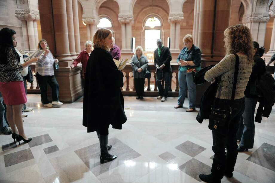 Maeve McEneny, center, a Capitol tour guide, leads a  ?Capitol Hauntings? tour of the New York State Capitol on Thursday, Oct. 11, 2012 in Albany, NY.  The annual tours explore the legends, folklore and ghost stories connected to the Capitol.  The ?Capitol Hauntings? tours are free and open to the public with tours being offered at noon Tuesday, October 9, to Friday, October 12, and at noon and 5:30 p.m. Monday through Friday, from October 15 to November 2.  The Capitol is closed Saturdays and Sundays.  Pre-registration is required and individuals and groups of 10 or less may register online at www.ogs.ny.gov. Larger parties may call 473-7582 to register.  (Paul Buckowski / Times Union) Photo: Paul Buckowski