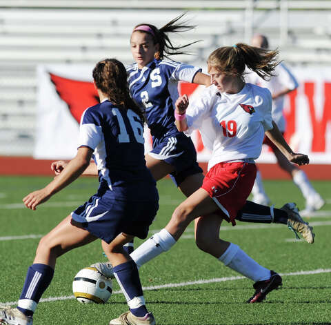 At right, , Megan Bartholomew # 19, of Greenwich, goes for the ball  while being pursued by  Staples players, Olivia Gerrard # 2, and Rebecca Bregman # 16, during the girls high school soccer match between Greenwich High School and Staples High School at Greenwich, Thursday, Oct. 11, 2012. Photo: Bob Luckey / Greenwich Time