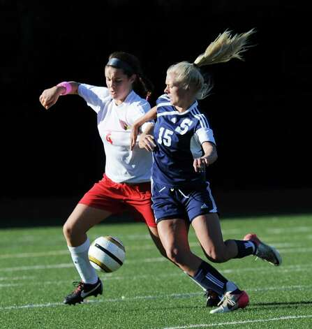At right, Ryan Kirshner of Staples # 15, goes for the ball against Caroline Markowitz # 4 of Greenwich during the girls high school soccer match between Greenwich High School and Staples High School at Greenwich, Thursday, Oct. 11, 2012. Photo: Bob Luckey / Greenwich Time