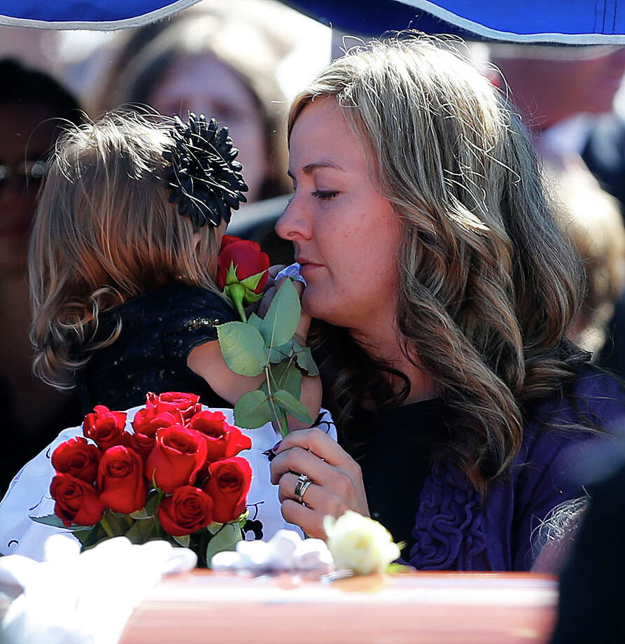 Christy Ivie (R) gives a flower to Presley Ivie, 22 months (L), wife and daughter of boarder patrol agent Nicholas Ivie, at a graveside service in Spanish Fork cemetery on October 11, 2012 in Spanish Fork, Utah. Ive was shot to death as he was patrolling the U.S. Mexican boarder on October 2, 2012 near Naco, Arizona. Photo: George Frey, Getty Images / 2012 Getty Images