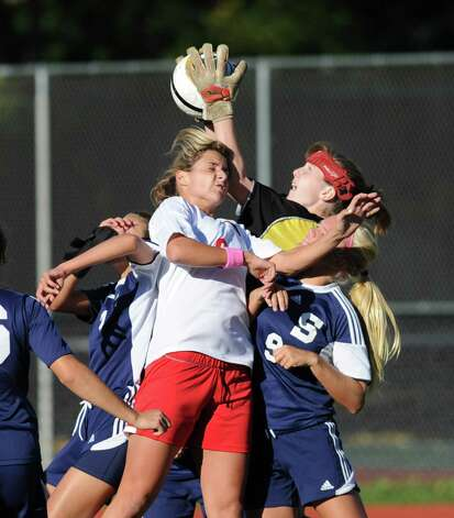 Staples goalie Allison Thomson goes atop Greenwich and Staples players to make a stop during the girls high school soccer match between Greenwich High School and Staples High School at Greenwich, Thursday, Oct. 11, 2012. Photo: Bob Luckey / Greenwich Time