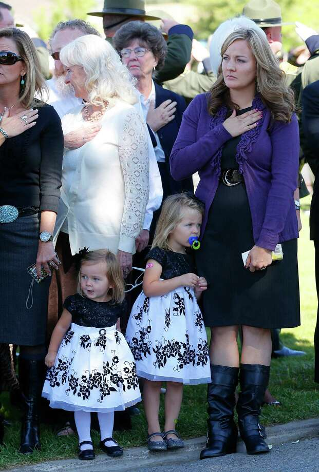 Christy Ivie (R), wife of boarder patrol agent Nicholas Ivie, stands at attention with her daughters Raigan (C), age 3 and Presley (L), 22 months, as they wait for her husbands casket to arrive for burial in Spanish Fork Cemetery on October 11, 2012 in Spanish Fork, Utah. Ive was shot to death as he was patrolling the U.S. Mexican boarder on October 2, 2012 near Naco, Arizona. Photo: George Frey, Getty Images / 2012 Getty Images
