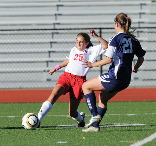 At left, Emily Berzolla # 25 of Greenwich advances the the ball as Gea Mitas # 21 of Staples defends during the girls high school soccer match between Greenwich High School and Staples High School at Greenwich, Thursday, Oct. 11, 2012. Photo: Bob Luckey / Greenwich Time