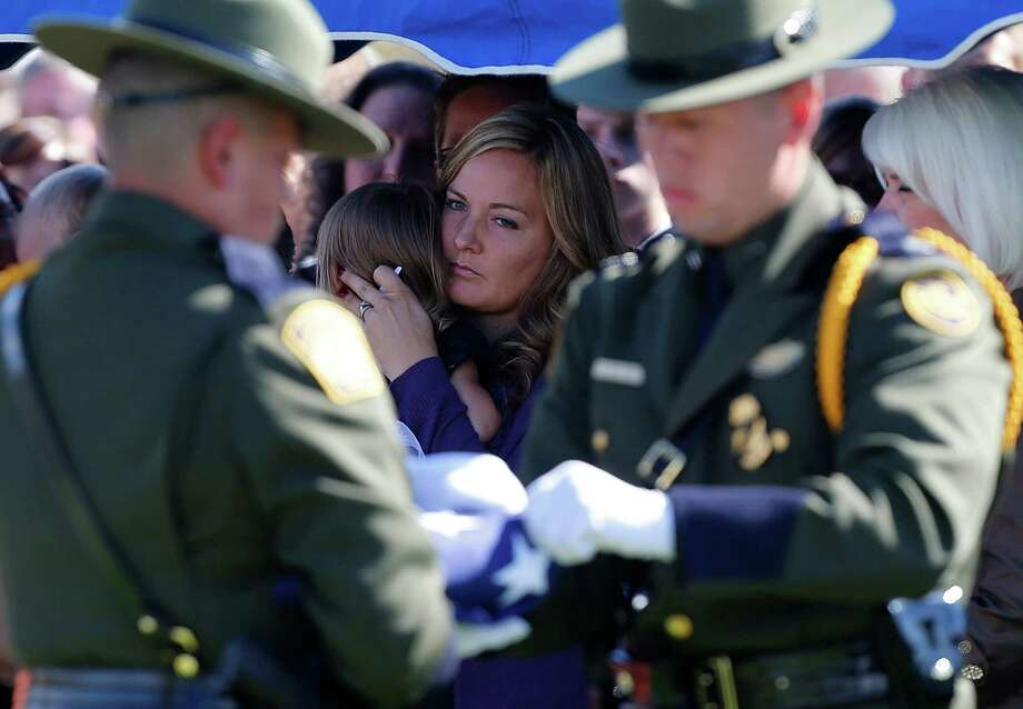 U.S. boarder patrol agents fold a flag off the casket of boarder patrol agent Nicholas Ivie, as his wife Christy Ivie (C) holds her daughter and watches at a graveside service in Spanish Fork cemetery on October 11, 2012 in Spanish Fork, Utah. Ive was shot to death as he was patrolling the U.S. Mexican boarder on October 2, 2012 near Naco, Arizona. Photo: George Frey, Getty Images / 2012 Getty Images