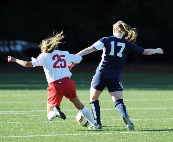 At left, Emily Berzolla # 25 of Greenwich goes for the ball against Maggie Walsh # 17 of Staples during the girls high school soccer match between Greenwich High School and Staples High School at Greenwich, Thursday, Oct. 11, 2012. Photo: Bob Luckey / Greenwich Time