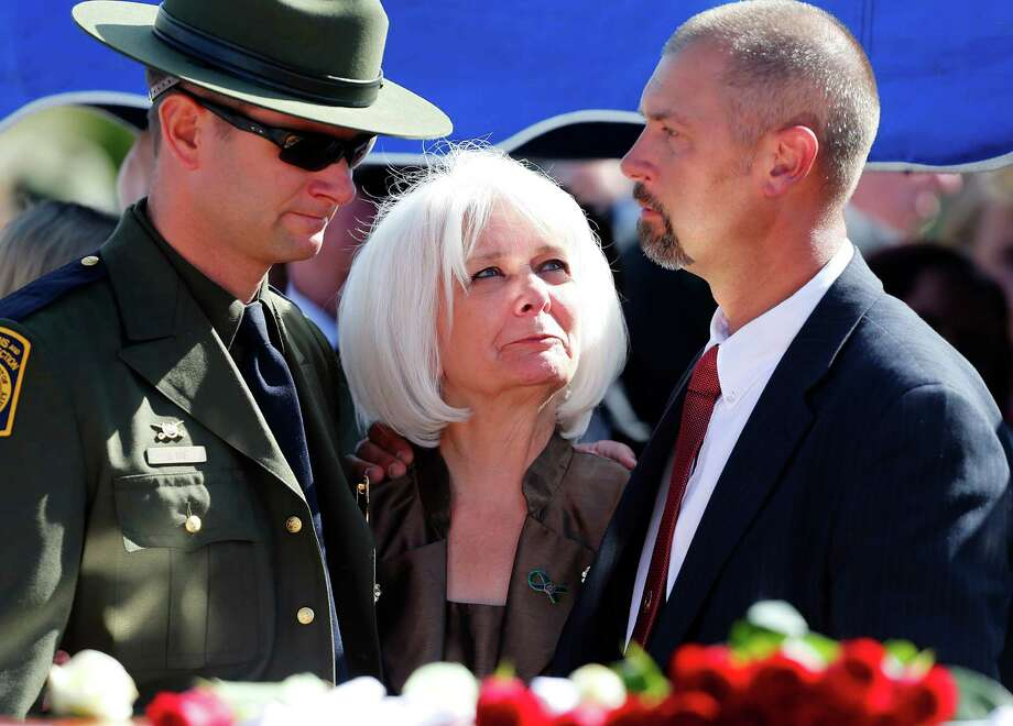 Joel Ivie, Cheryl Ivie, and Cheis Ivie, family members of boarder patrol agent Nicholas Ivie, pause at Ivie's casket at a graveside service in Spanish Fork cemetery on October 11, 2012 in Spanish Fork, Utah. Ive was shot to death as he was patrolling the U.S. Mexican boarder on October 2, 2012 near Naco, Arizona. Photo: George Frey, Getty Images / 2012 Getty Images