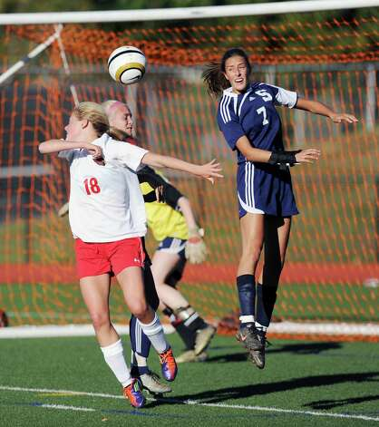 At left, Isbella Pehrson # 18 of Greenwich goes for the header as does Meghan Lonergan # 7 of Staples during the girls high school soccer match between Greenwich High School and Staples High School at Greenwich, Thursday, Oct. 11, 2012. Photo: Bob Luckey / Greenwich Time