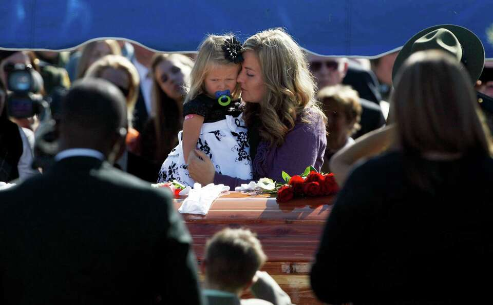 Christy Ivie holds her daughter Raigan, 3, as she stands by the casket containing her husband, borde