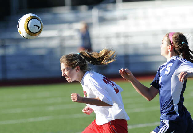 At left, Megan Bartholomew # 19, of Greenwich, goes for the header while being pursued by a Staples player Olivia Gerrard # 2 during the girls high school soccer match between Greenwich High School and Staples High School at Greenwich, Thursday, Oct. 11, 2012. Photo: Bob Luckey / Greenwich Time