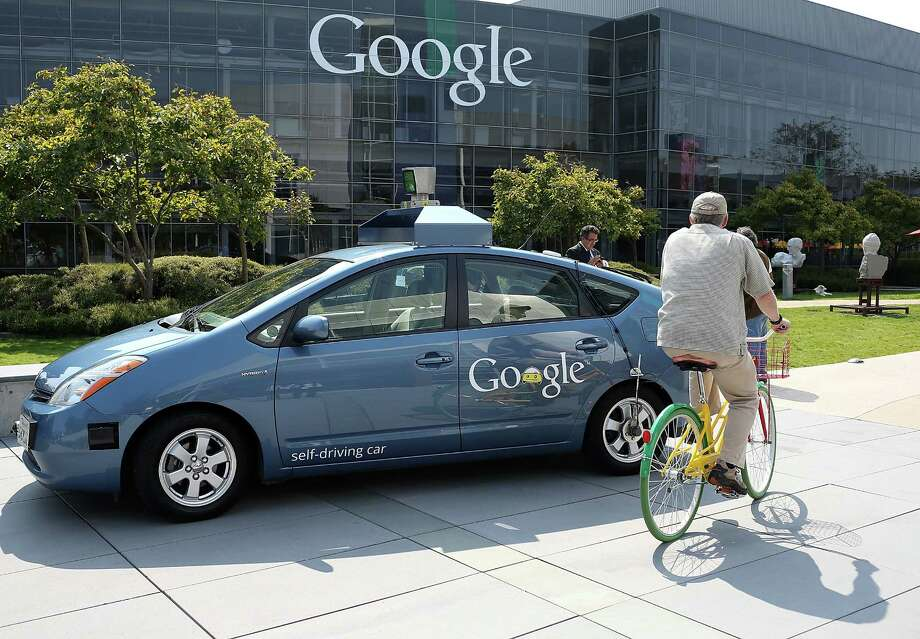 MOUNTAIN VIEW, CA - SEPTEMBER 25:  A bicyclist rides by a Google self-driving car at the Google headquarters on September 25, 2012 in Mountain View, California.  California Gov. Jerry Brown signed State Senate Bill 1298 that allows driverless cars to operate on public roads for testing purposes. The bill also calls for the Department of Motor Vehicles to adopt regulations that govern licensing, bonding, testing and operation of the driverless vehicles before January 2015. Photo: Justin Sullivan, Getty Images / 2012 Getty Images