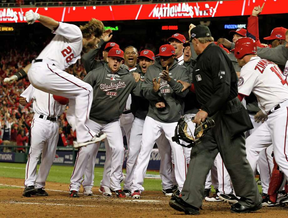 The Nationals' Jayson Werth leaps toward home plate where his teammates wait to mob him after hitting the game-winning home run in the ninth inning. Photo: Alex Brandon / AP