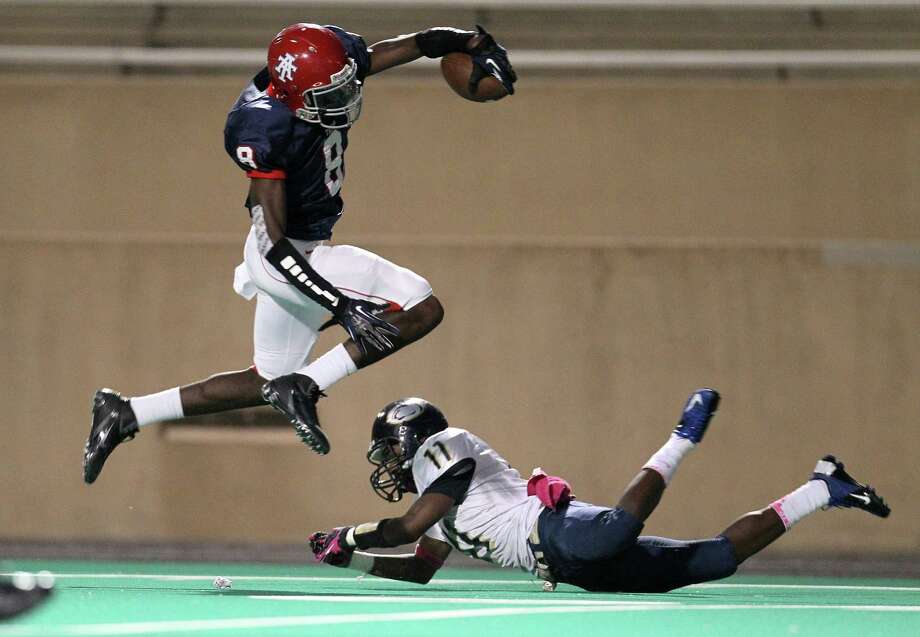 Alief Taylor's Keenen Brown (8) leaps over Nimitz's Marcus Starghill (11) on his way to the end zone for a touchdown during the first half of the Nimitz High school football game played against Alief Taylor at Crump Stadium, Thursday, Oct. 11, 2012, in Houston. Photo: Karen Warren, Houston Chronicle / © 2012  Houston Chronicle