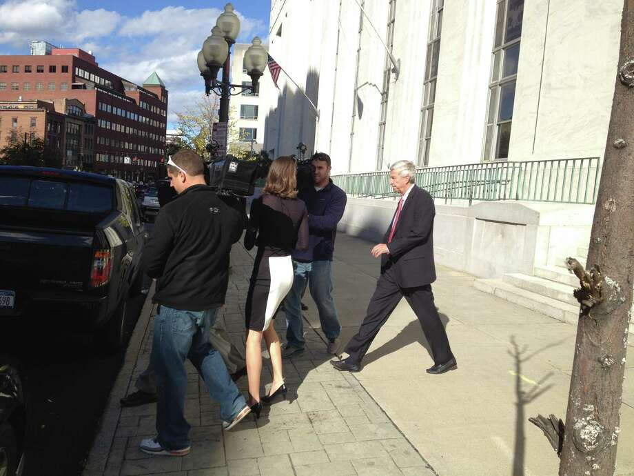 David L. Smith, right, leaves U.S. District Court in Albany on Thursday afternoon following their arraignment on a 32-count superseding indictment. The longtime business partners, co-founders of McGinn, Smith & Co., are accused of defrauding hundreds of investors of more than $100 million. The charges include conspiracy, mail and wire fraud, and filing false tax returns. (Brendan Lyons / Times Union)