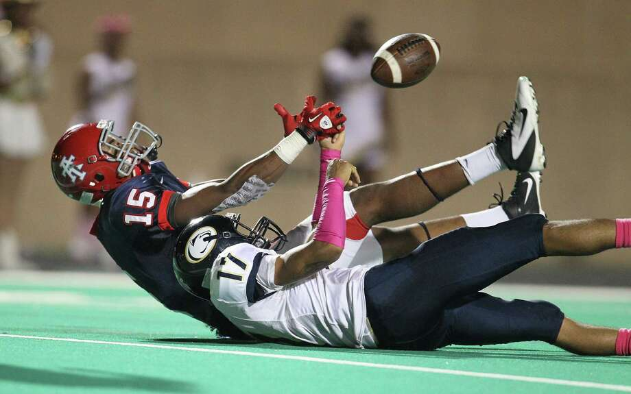 Alief Taylor's Romello Brooker (15) and  Nimitz's Deon Griffin (17) battle on the ground for an incomplete pass intended for Brooker during the first half of the Nimitz High school football game played against Alief Taylor at Crump Stadium, Thursday, Oct. 11, 2012, in Houston. Photo: Karen Warren, Houston Chronicle / © 2012  Houston Chronicle