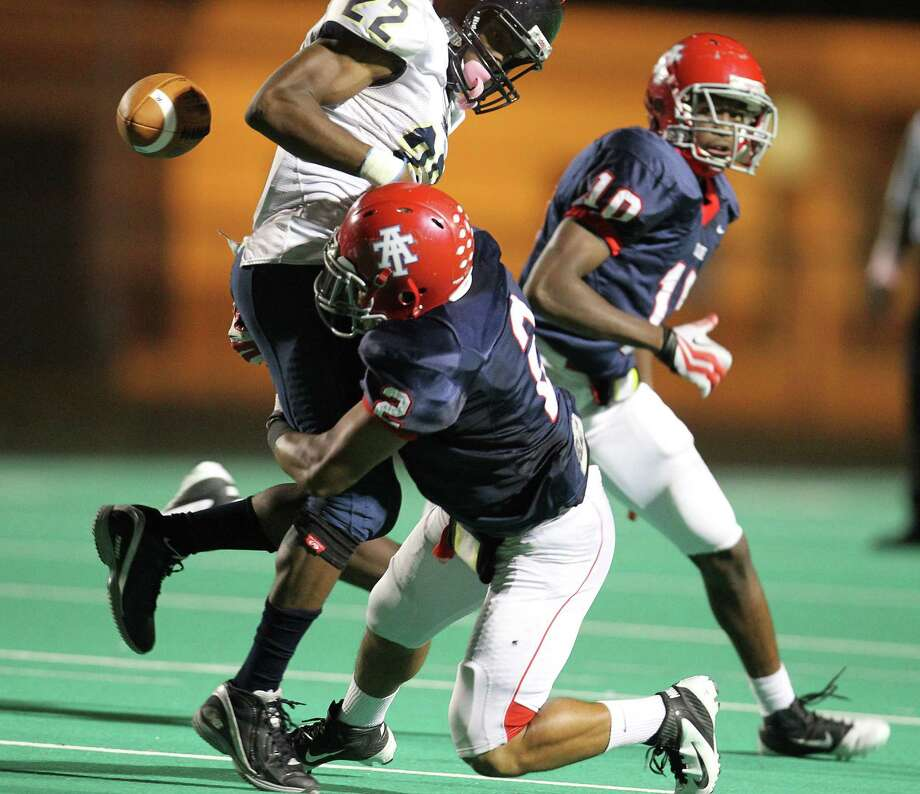Nimitz's Dre'Vian Young (22) gets the ball knocked loose by Alief Taylor's Chris Hardeman (2) during the first half of the Nimitz High school football game played against Alief Taylor at Crump Stadium, Thursday, Oct. 11, 2012, in Houston. Photo: Karen Warren, Houston Chronicle / © 2012  Houston Chronicle