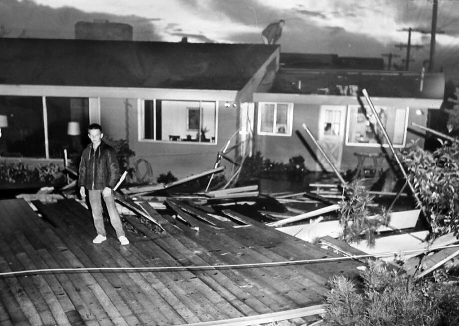 This photo caption from Sept. 28, 1962 read: Splintered carport roof of one-inch planking together with supporting 4 by 8-inch beams lies in backyard of William Gates home, 7308 44th Ave. N.E. first to feel sting of tornado last evening. The roof, surveyed here by Mike Patterson, 13, a neighbor boy, few up and over Gates home to crash landing in backyard. Photo: Tom Brownell/seattlepi.com File/MOHAI