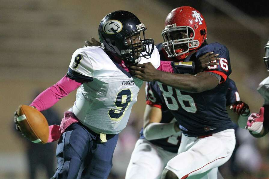 Nimitz's QB Floyd Allen (9) nearly gets tackled by Alief Taylor's Torrodney Prevot (86) during the s