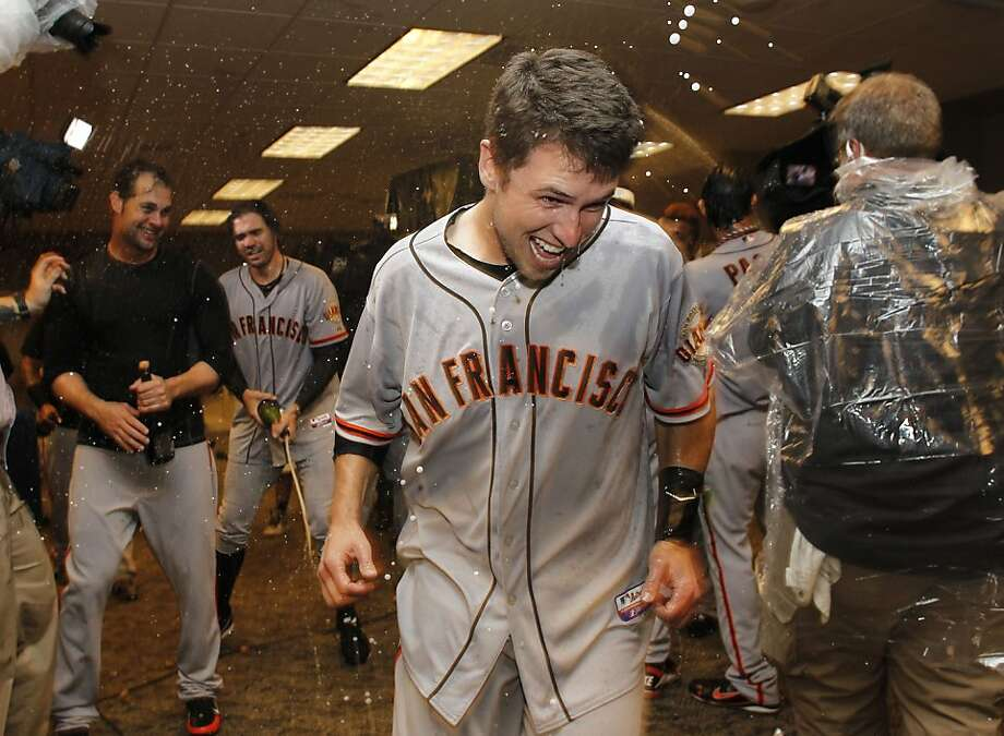 Giants' Buster Posey escapes a spray of champagne as the team celebrates in the clubhouse, as the San Francisco Giants beat the Cincinnati Reds 6-4 in game five to win the National League Division Series in Cincinnati, Ohio on Thursday Oct. 11, 2012. Photo: Michael Macor, The Chronicle
