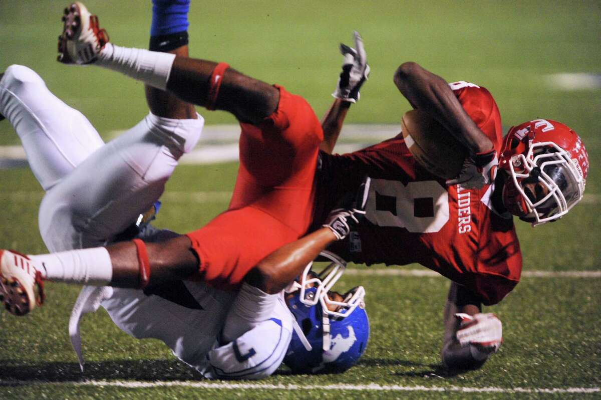 Receiver P.J. Anderson of Taft (8) is tackled by Dae Ross (7) of Jay during District 27-5A football action at Farris Stadium on Thursday, Oct. 11, 2012.