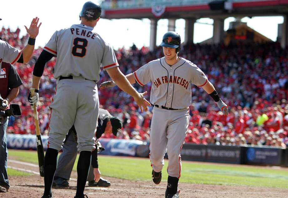 The Giants' Buster Posey, right, is greeted at home by Hunter Pence after hitting a fifth-inning grand slam that helped eliminate the Reds in Game 5 of their National League Division Series on Friday in Cincinnati. Photo: Patrick Tehan / San Jose Mercury News