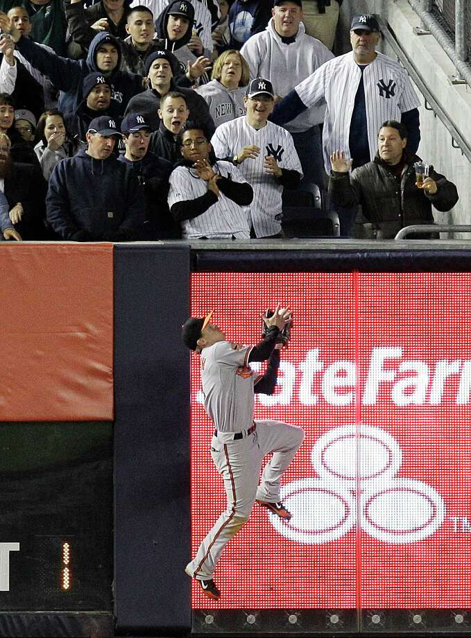 New York Yankees fans react as Baltimore Orioles left fielder Nate McLouth catches a ball hit by Yankees' Jayson Nix during the fifth inning of Game 4 of the American League division baseball series on Thursday, Oct. 11, 2012, in New York. Yankees' Russell Martin was out at first base for a double play.  (AP Photo/Kathy Willens) Photo: Kathy Willens