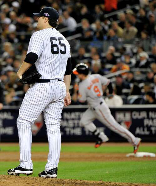 New York Yankees starting pitcher Phil Hughes (65) reacts as Baltimore Orioles' Nate McLouth, right,