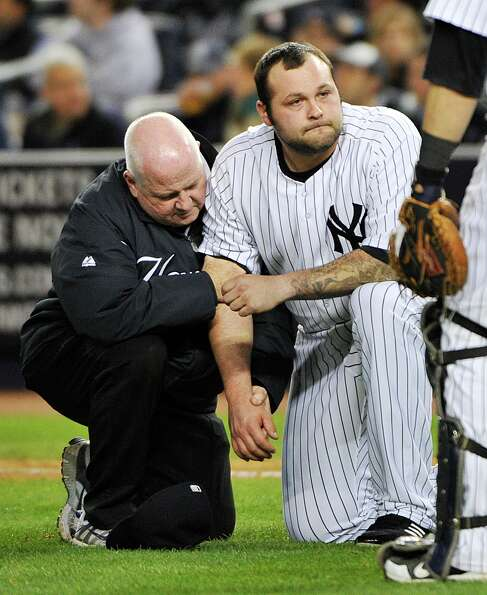 A trainer, left, helps New York Yankees relief pitcher Joba Chamberlain who was hit by a broken bat