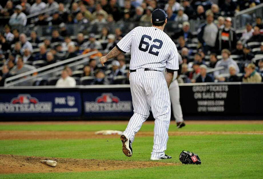 New York Yankees relief pitcher Joba Chamberlain (62) reacts after being hit by a broken bat as Baltimore Orioles' Matt Wieters (32) hit a single during the twelfth inning of Game 4 of the American League division baseball series on Thursday, Oct. 11, 2012, in New York. (AP Photo/Bill Kostroun) Photo: Bill Kostroun