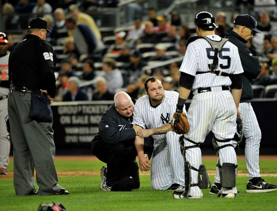 Trainers help New York Yankees relief pitcher Joba Chamberlain, third from right, reactsafter he was hit by a broken bat when Baltimore Orioles' Matt Wieters hit a single during the twelfth inning of Game 4 of the American League division baseball series on Thursday, Oct. 11, 2012, in New York. (AP Photo/Bill Kostroun) Photo: Bill Kostroun