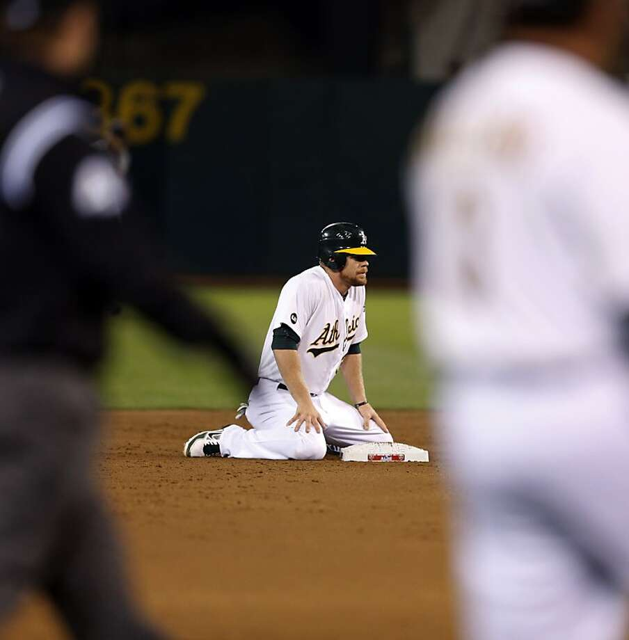 Brandon Moss sits on the base defected after being called out on a steal in the bottom of the second inning. The Oakland Athletics played the Detroit Tigers in game 5 of the ALDS at O.co Coliseum in Oakland, Calif. on Thursday, October 11, 2012. Photo: Beck Diefenbach, Special To The Chronicle