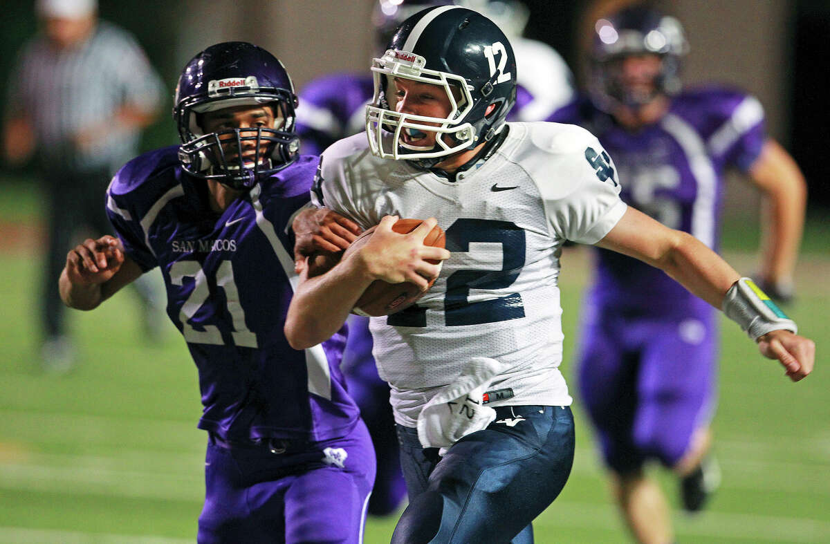 Rangers quarterback Garrett Smith rolls for a first down past the Rattlers' Nick Manrique as San Marcos plays Smithson Valley at Bobcat Stadium in San Marcos on Oct. 11, 2012.