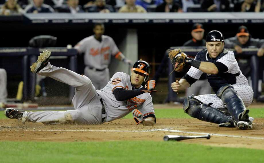 Baltimore Orioles' Manny Machado, left, is tagged out at home plate by New York Yankees catcher Russell Martin during the third inning of Game 4 of the American League division baseball series on Thursday, Oct. 11, 2012, in New York. (AP Photo/Kathy Willens) Photo: Kathy Willens